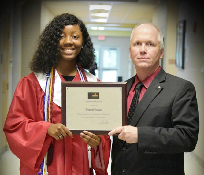 Mr. Burnette is presenting a plaque to Briannah, who is dressed in her graduation gown.